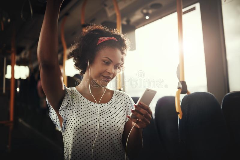 Smiling young African woman listening to music on a bus royalty free stock photos