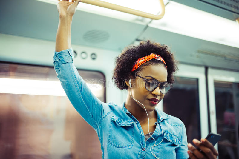Smiling young African woman listening to music on the subway royalty free stock photos
