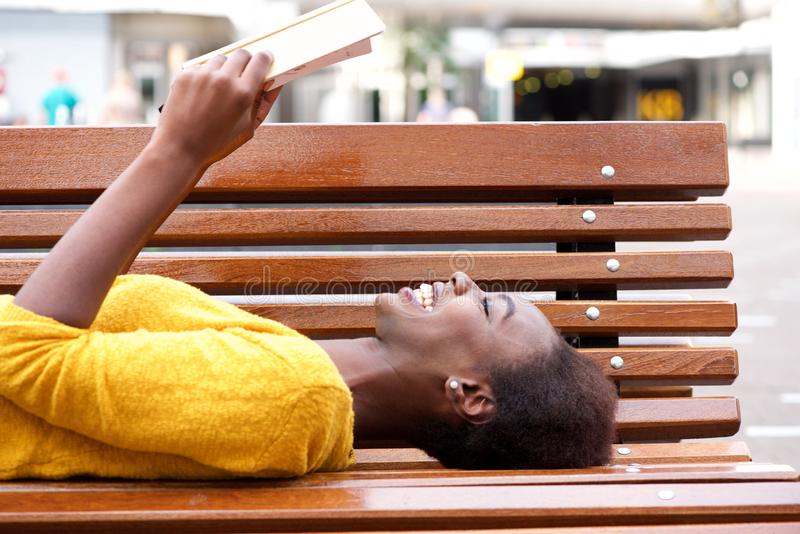 Smiling young african woman lying on bench reading book royalty free stock image