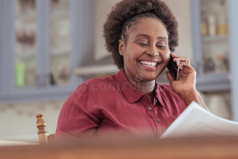 Smiling African woman reading paperwork and talking on her cellphone royalty free stock image