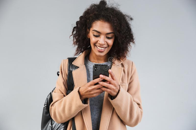 Smiling young african woman wearing coat. Using mobile phone while standing isolated royalty free stock photo