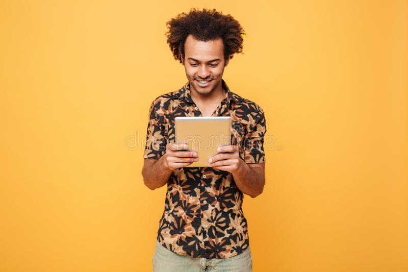 Smiling young afro american guy standing and using pc tablet stock photo