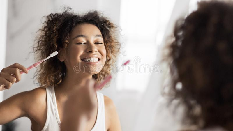 Healthy teeth concept. Smiling young afro woman with toothbrush cleaning teeth at bathroom. Healthy teeth concept stock photo