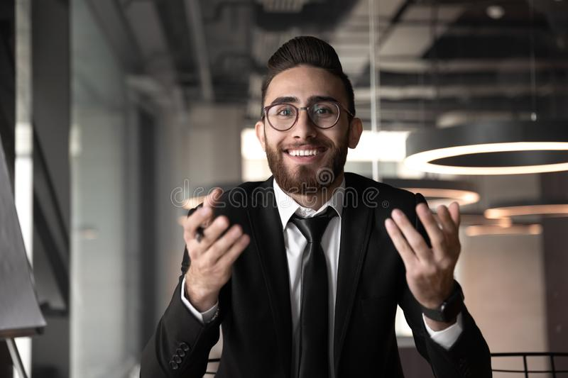 Smiling Arabian businessman having video call in office. Smiling young Arabian businessman in glasses sit at office desk speak on video call with business stock photo