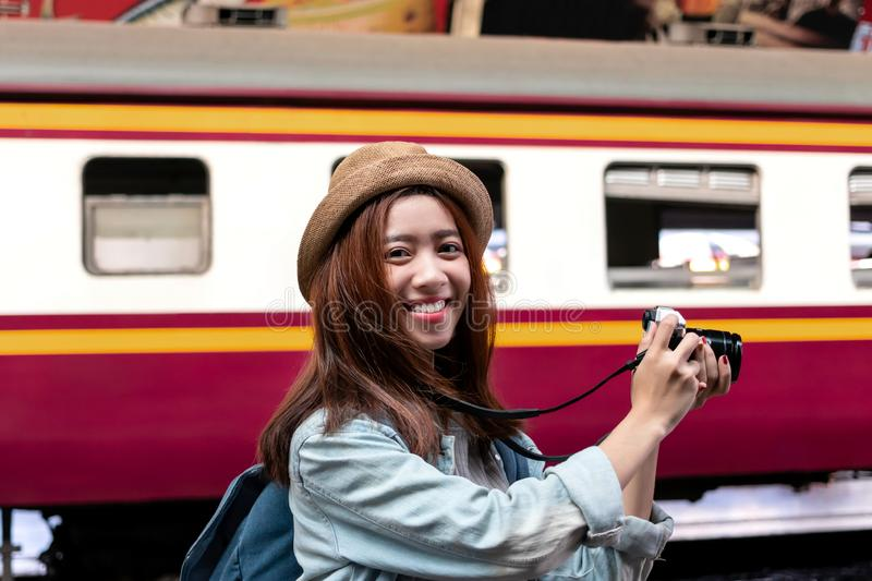 Smiling young Asian backpacker female holding digital camera at train station. Travel lifestyle concept stock photo
