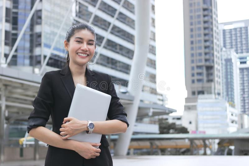 Smiling young Asian business woman with laptop at outside office.  stock image