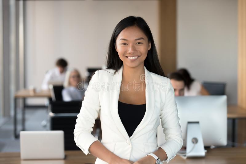 Smiling young asian business woman looking at camera in office stock photos