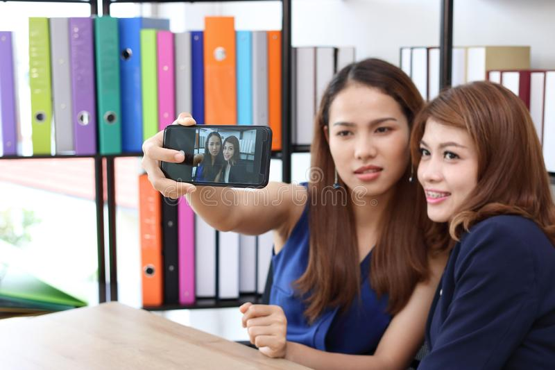 Smiling young Asian business women taking a picture or selfie together in office. stock photography