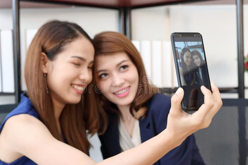 Smiling young Asian business women taking a picture or selfie together in office stock images