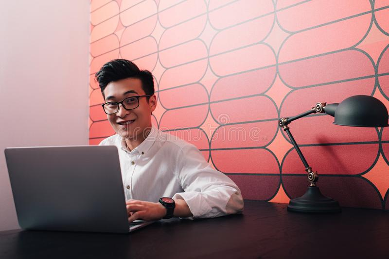 smiling young asian businessman working at table with laptop royalty free stock photos