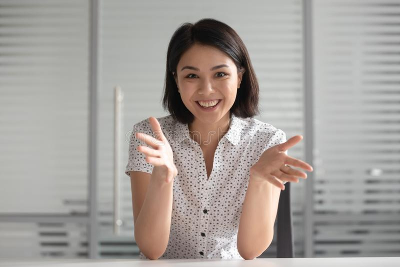 Smiling young Asian businesswoman looking at camera and talking royalty free stock image