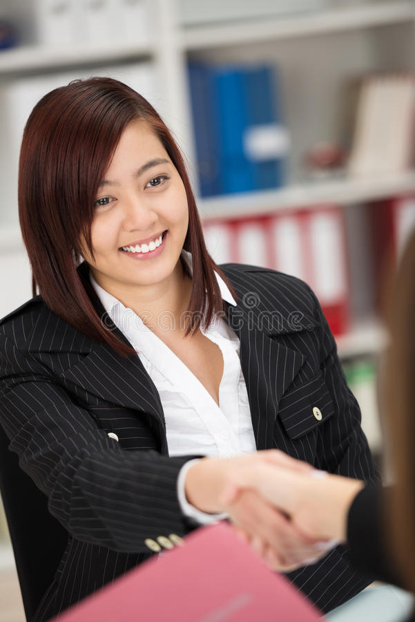 Smiling young Asian businesswoman shaking hands. Across a desk in the office with another woman as they seal a deal or shake hands on a partnership stock photography