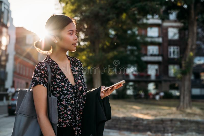 Young Asian businesswoman standing outside after work using her cellphone stock photo