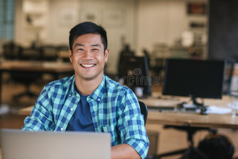 Smiling young Asian designer using a laptop at his desk royalty free stock photo