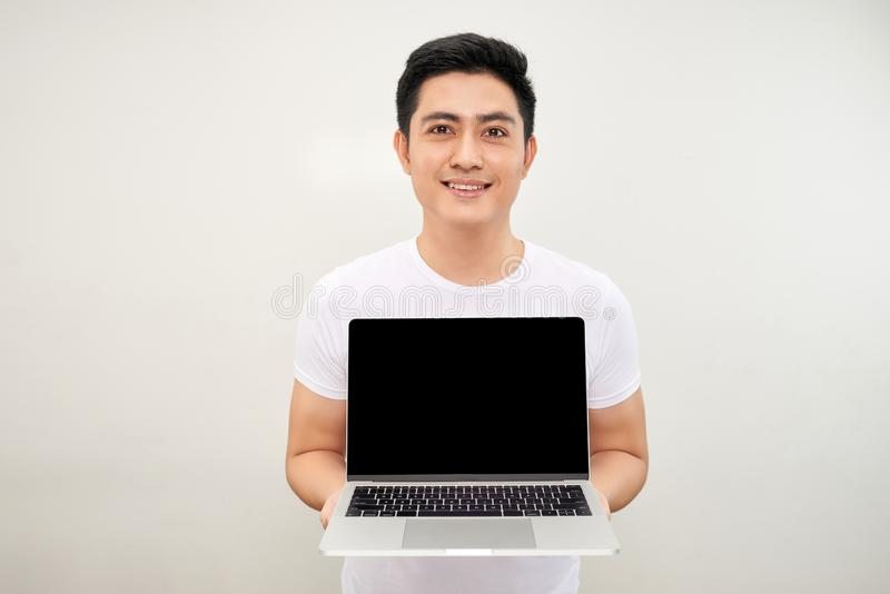 Smiling young asian man dressed in shirt showing blank screen laptop computer over white background stock images