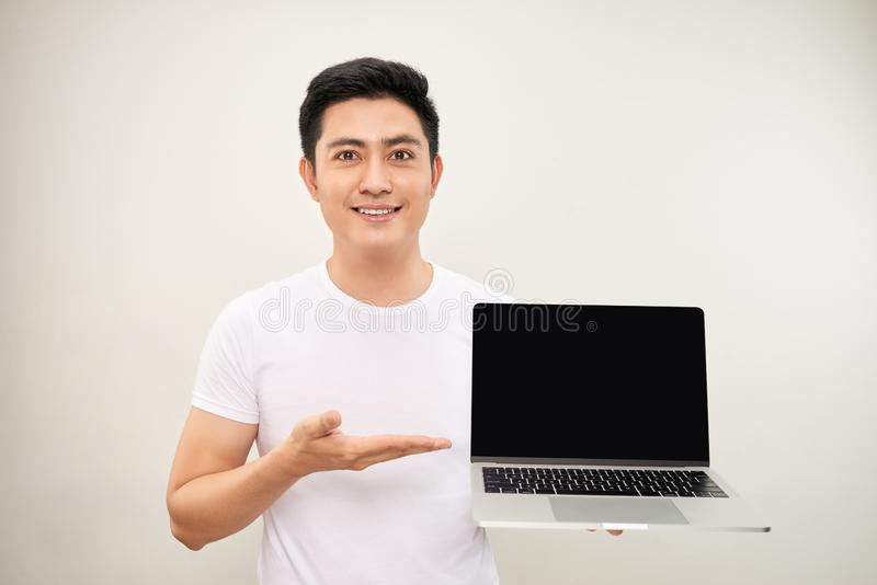 Smiling young asian man dressed in shirt showing blank screen laptop computer over white background stock photo