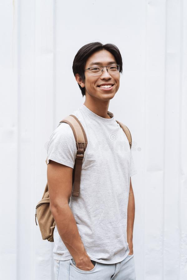 Smiling young asian man student carrying backpack royalty free stock photo