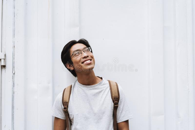 Smiling young asian man student carrying backpack royalty free stock photography