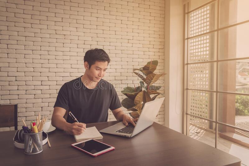 Smiling young asian man wear casual clothing while sitting at big wooden table in modern kitchen, working with laptop at home royalty free stock images