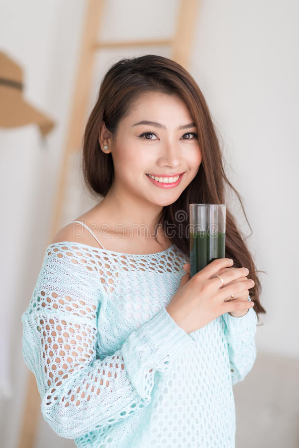 Smiling young asian woman drinking green fresh vegetable juice o. R smoothie from glass at home royalty free stock photos