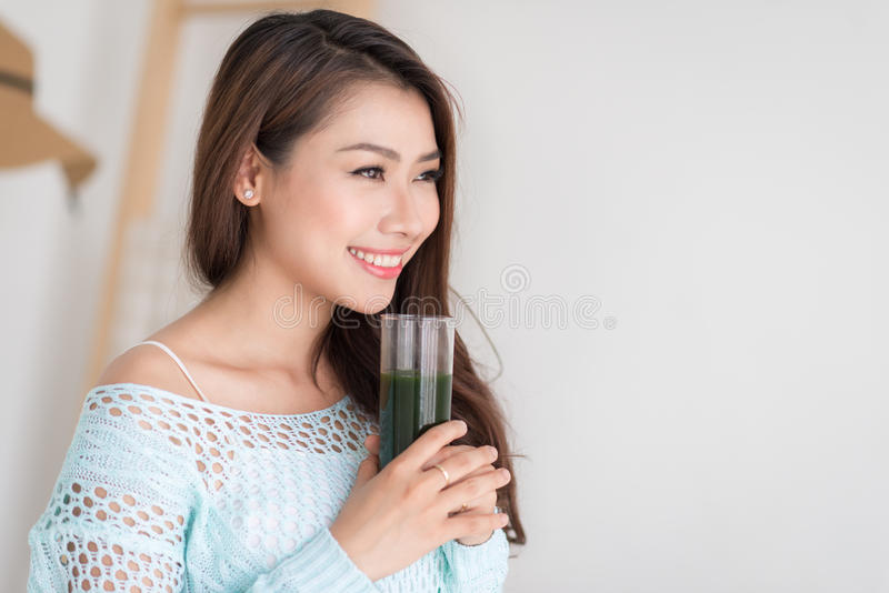 Smiling young asian woman drinking green fresh vegetable juice o royalty free stock images