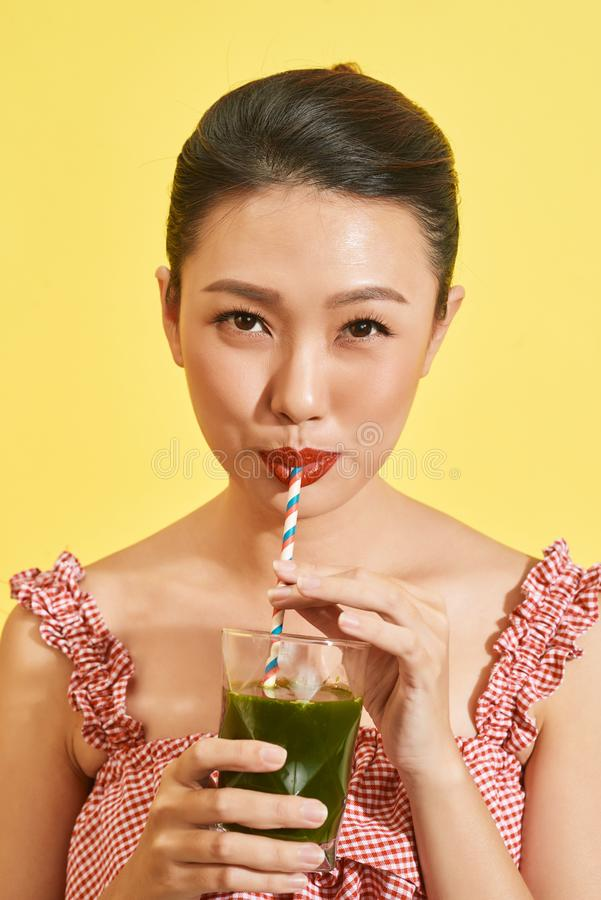 Smiling young asian woman drinking green fresh vegetable juice or smoothie from glass.  royalty free stock photography