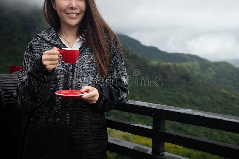 Smiling young asian woman drinking hot coffee on scenery view in morning, front view. Smiling young asian woman drinking hot coffee on scenery view in morning stock photography