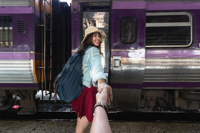 Smiling young Asian woman holding boyfriend hands follow her at train station. Romantic and travel in summer vacation concept royalty free stock photo
