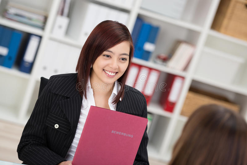 Smiling young Asian woman in a job interview. Sitting talking to the employment officer with her curriculum vitae in her hands royalty free stock photo