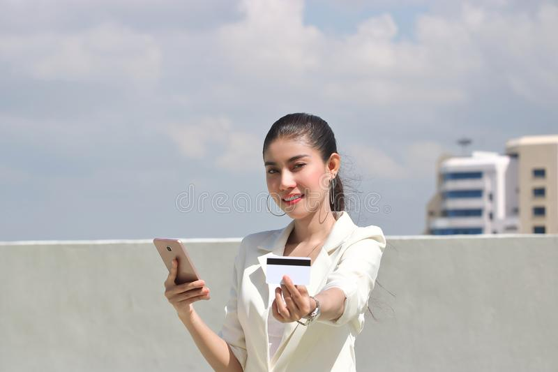 Smiling young Asian woman with mobile smart phone and credit card for shopping online stock photos