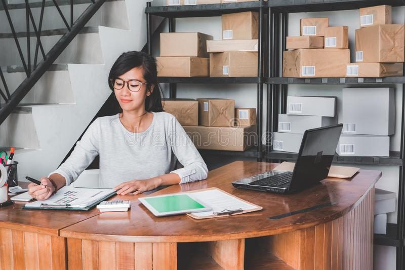 Online shop seller working at home office. Smiling young asian woman in package shelf. online shop seller at home office royalty free stock photography