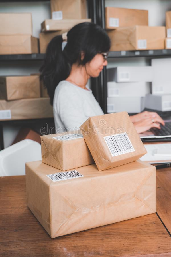 Online shop seller working at home office. Smiling young asian woman in package shelf. online shop seller at home office stock photo