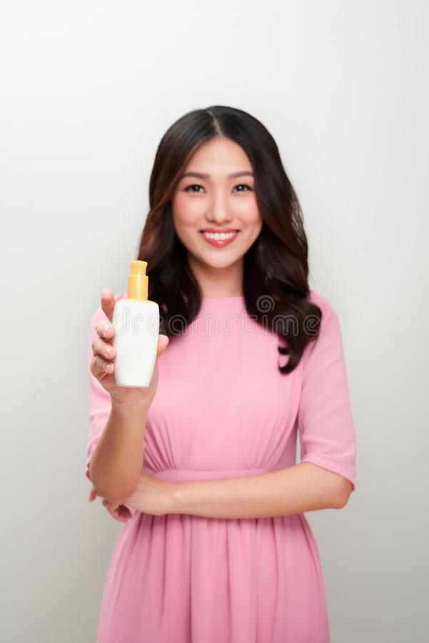 Smiling young asian woman showing skincare product. Smiling young asian woman showing skincare product royalty free stock photos