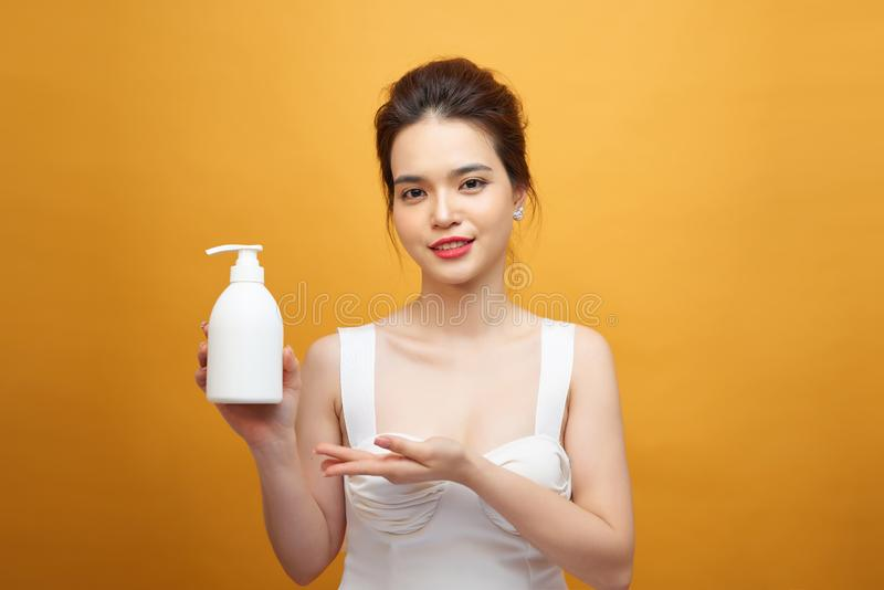 Smiling young asian woman showing skincare product on yellow background.  royalty free stock image
