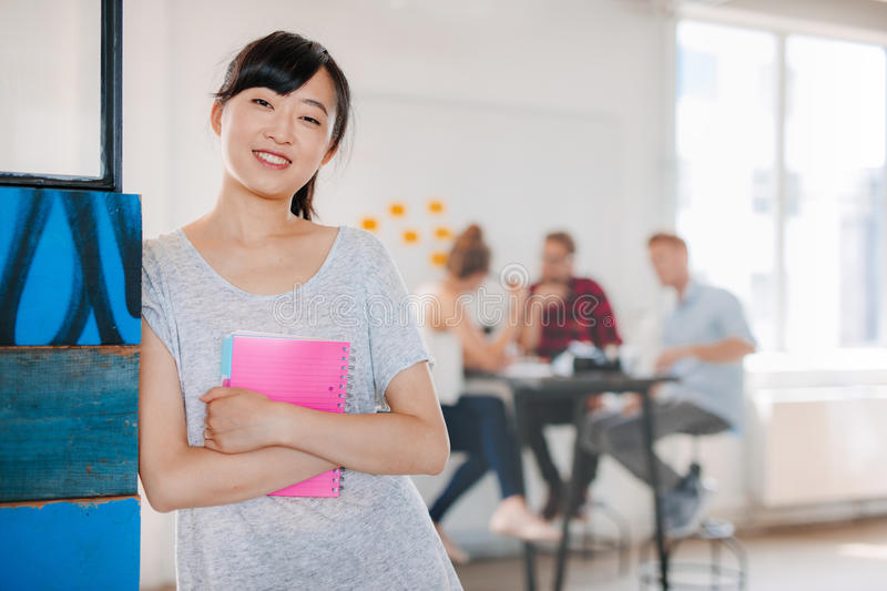 Smiling young asian woman standing in office royalty free stock photography
