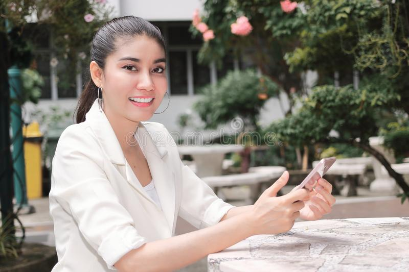 Smiling young Asian woman using mobile smart phone. Internet of things concept stock photos