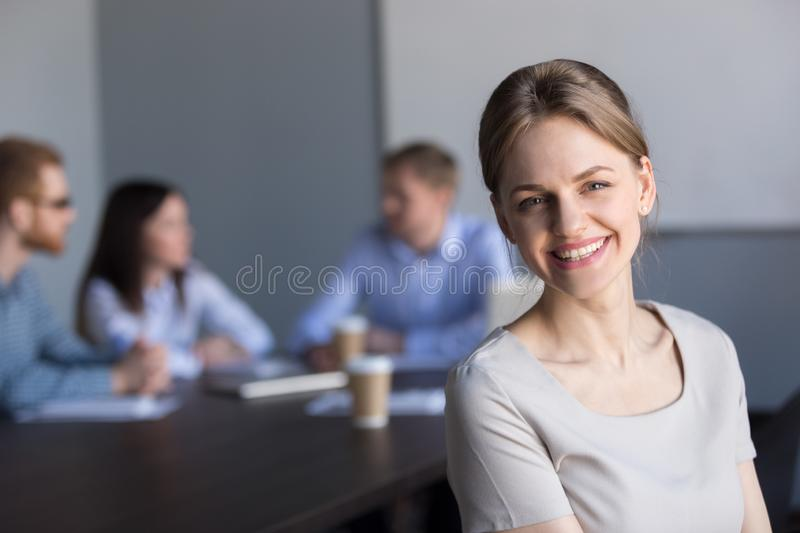 Smiling young attractive professional businesswoman looking at c. Amera in office with colleagues at background, happy successful female business leader, coach stock photo