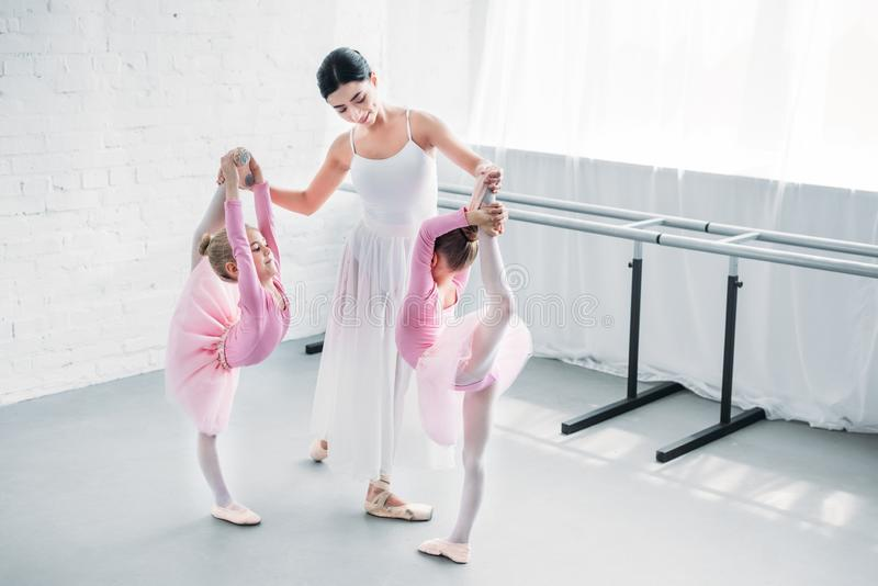 Smiling young ballet teacher exercising with kids. In ballet school stock image
