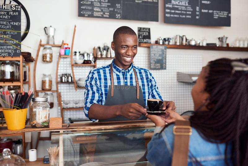 Smiling young barista handing coffee to a cafe customer royalty free stock photos