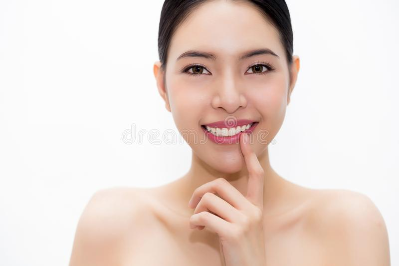 Smiling young and beautiful Asian woman pointing to white teeth royalty free stock image