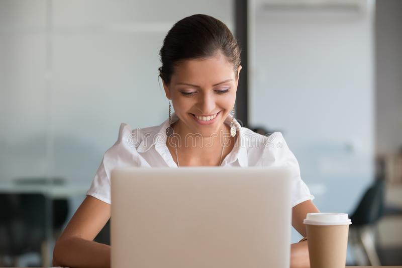 Smiling young beautiful female professional secretary using laptop at workplace stock image