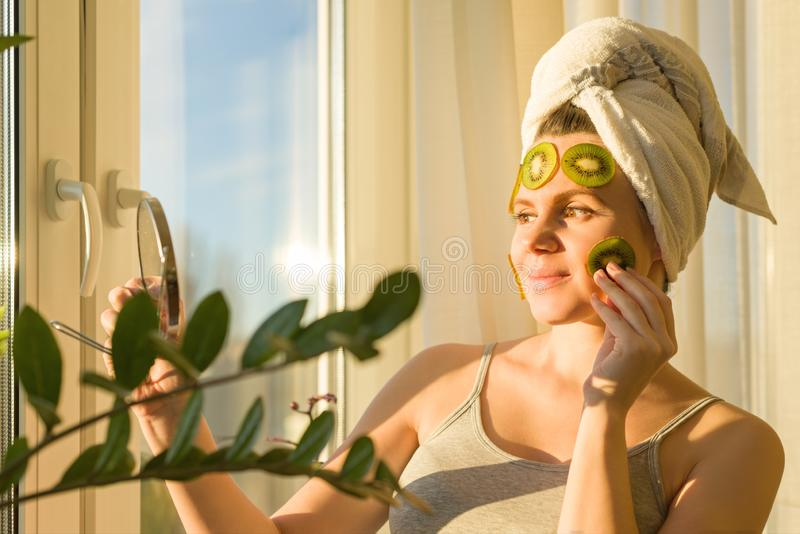 Smiling young beautiful woman close up at home near the window with natural homemade fruit facial mask of kiwi on face, towel on stock photography
