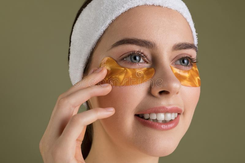 Smiling young beautiful woman in gold patches for eyes on green  background. Face skin care concept stock image