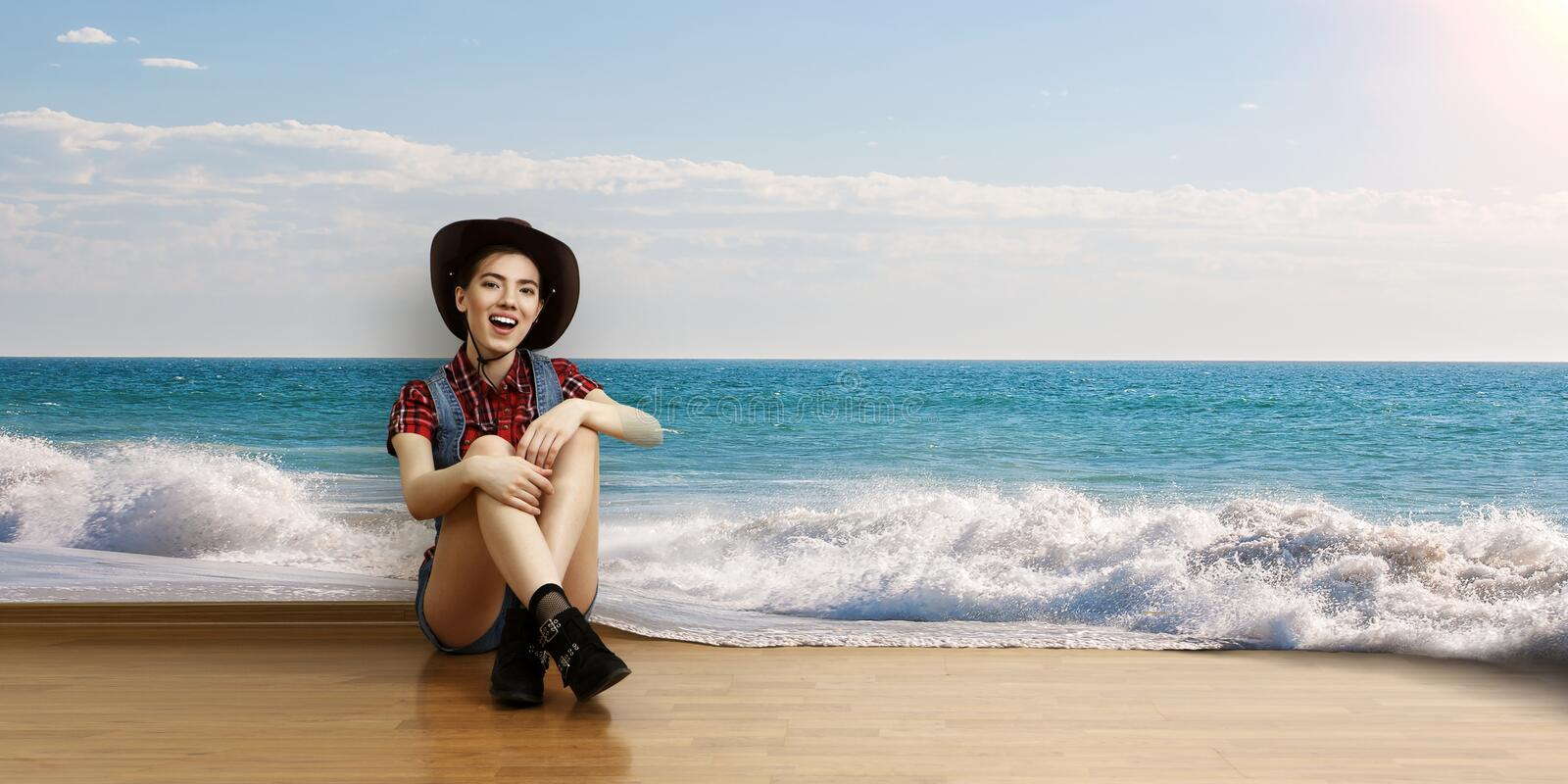 Smiling young beautiful woman sitting on the floor. Mixed media royalty free stock photography