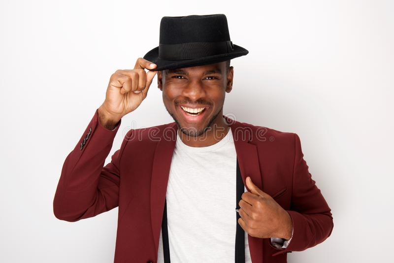 Smiling young black man posing with hat and blazer by white background. Portrait of smiling young black man posing with hat and blazer by white background royalty free stock photos