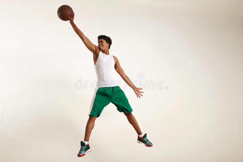 Smiling young black man reaching high for a basketball stock photo