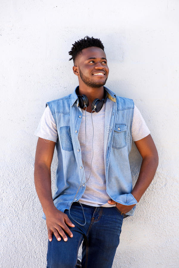 Smiling young black man standing by white wall with head phones royalty free stock photography