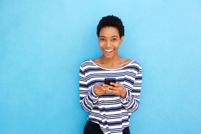 Smiling young black woman holding cellphone by blue background royalty free stock images