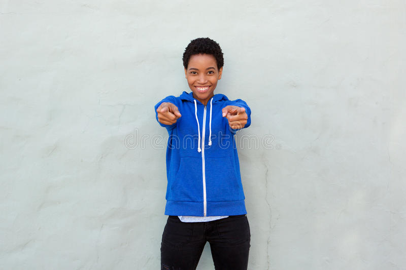 Smiling young black woman pointing fingers at you royalty free stock photography