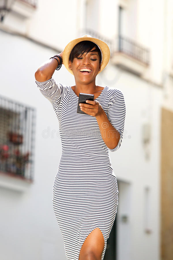 Smiling young black woman reading text message on cell phone royalty free stock photos